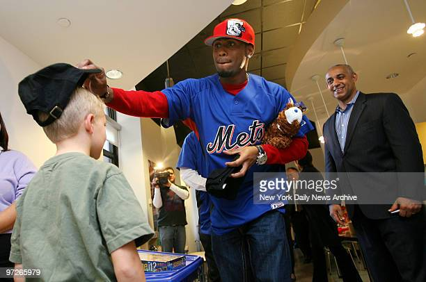 New York Mets' shortstop Jose Reyes puts a Mets cap on a child as Mets' general manager Omar Minaya looks on at The Zone a therapeutic and...