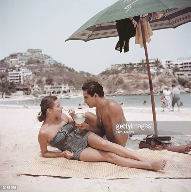 New York model Jean Adams and friend share a drink on the beach at Acapulco