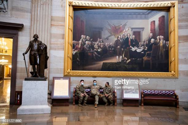 New York National Guard troops hang out under a painting of the Declaration of Independence painting by John Trumbull in the Capitol Rotunda on the...