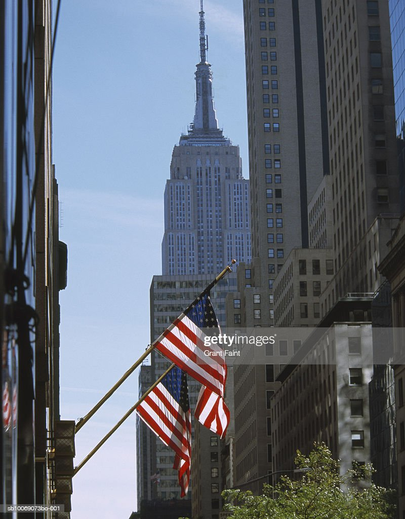 USA, New York, New York City, American flags on building, Empire State Building in background : Stockfoto
