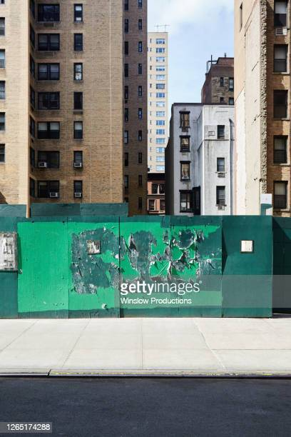 usa, new york, new york city, buildings with poster wall in foreground - new york city stock pictures, royalty-free photos & images