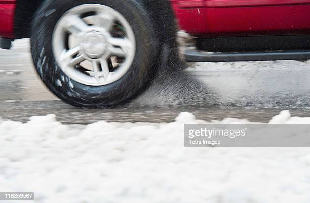 USA, New York, New York City, close up of car's wheels on road in winter