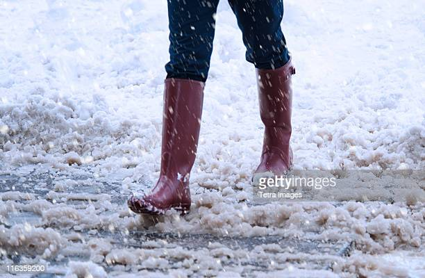 USA, New York, New York City, close up of woman's legs walking in winter slush