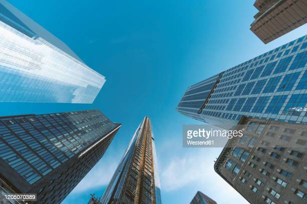 usa, new york, new york city, directly below view of clear sky over manhattan skyscrapers - manhattan new york city stock pictures, royalty-free photos & images