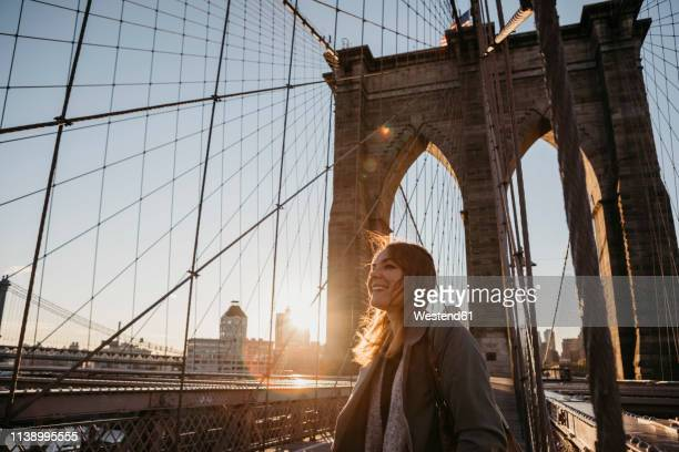 usa, new york, new york city, female tourist on brooklyn bridge at sunrise - new york state stock pictures, royalty-free photos & images