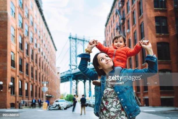 usa, new york, new york city, mother and baby in brooklyn with manhattan bridge in the background - baby human age stock pictures, royalty-free photos & images