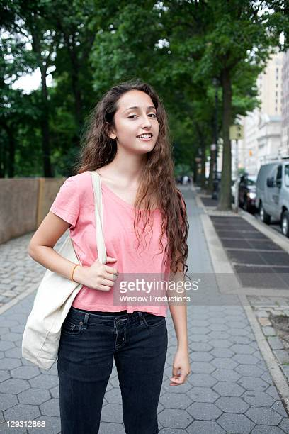 USA, New York, New York City, Portrait of smiling young woman standing on street