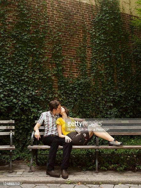 stati uniti, new york, new york city, giovane coppia baciare sulla panchina pubblica - panchina foto e immagini stock