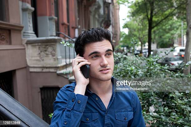 USA, New York, New York City, Young man talking on mobile phone on street