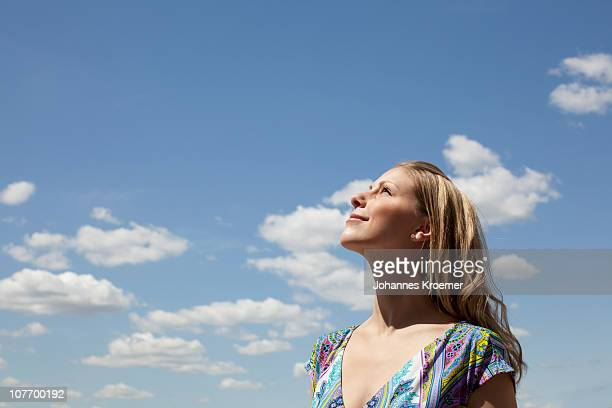 USA, New York, New York City, Young woman smiling against cloudy sky