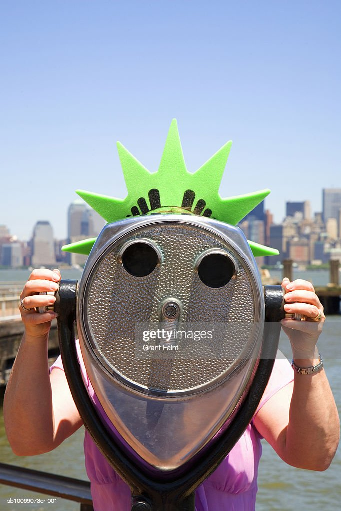 USA, New York, New York City, young woman wearing liberty crown headwear looking through telescope : Stockfoto