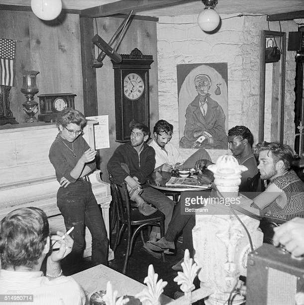 Inside the Beatnik street level coffee shop the Beatniks make their own entertainment At the moment all eyes are on the girl standing by the piano...