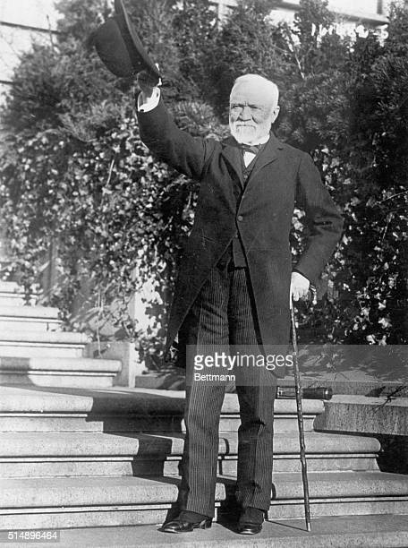 Picture shows industrialist Andrew Carnegie standing on the steps of his estate wearing a suit and waving his hat Undated photo circa 1910s