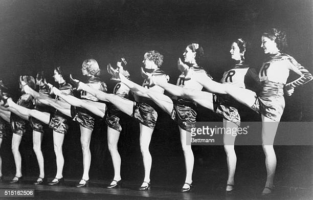 The Rockettes on stage at Radio city Music Hall with the letter R on their costumes and legs raised for their classic chorus line performance