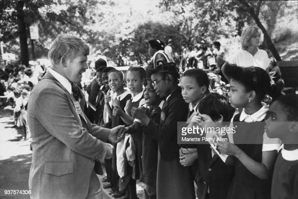 New York, New York - Tuesday, June 11, 1981: African-American children in school uniforms are greeted by the Grand Marshall of the 'Conquest 80s...