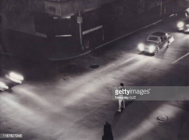 New York City police officer illuminated by headlights directs traffic at the intersection of Madison Avenue and E. 79th St. During a blackout on...
