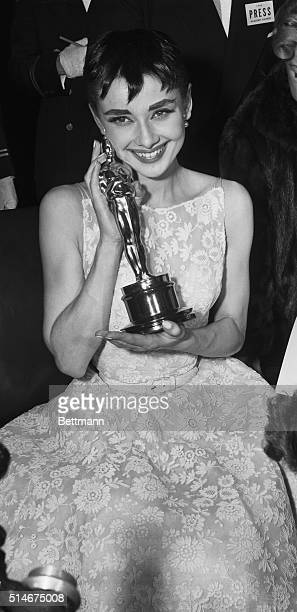 3/25/1954 New York NY Audrey cuddles up to Oscar Audrey Hepburn who rushed from her hit Broadway play Ondine to receive the Academy Award as Best...