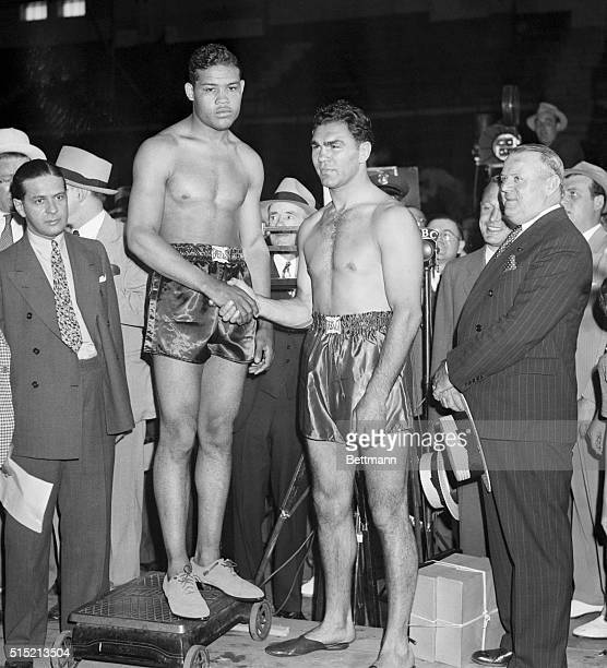 New York, NY - Champion Joe Louis shakes the hand of Max Schmeling--the same hand that put him to sleep last time they met- at the weighing-cereony...