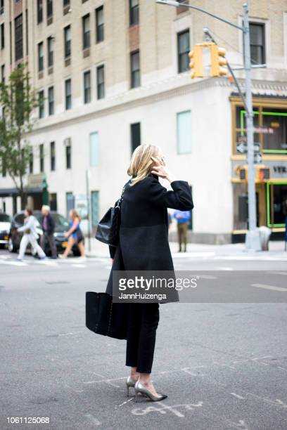new york, ny: chic woman hailing taxicab, madison avenue - madison avenue stock pictures, royalty-free photos & images