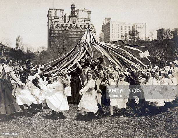 Children celebrating May Day in Central Park by dancing around a Maypole Undated Photograph circa 1900