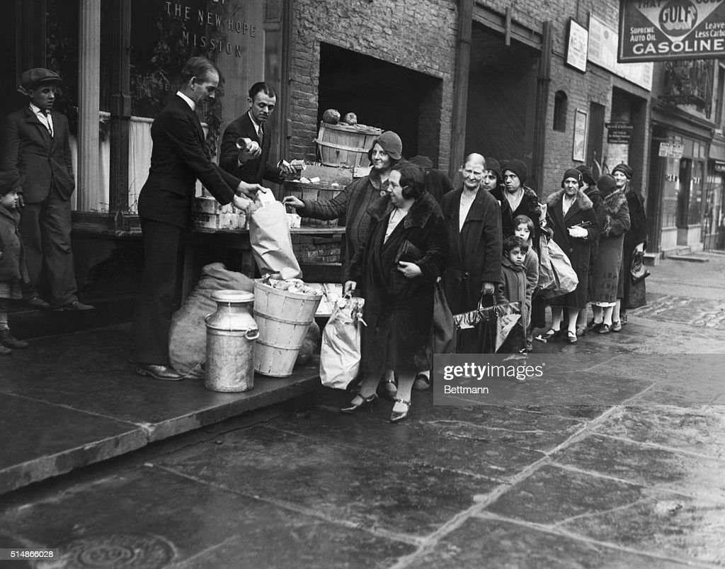 Women of unemployed workers receiving food from priests of ...