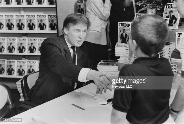 Donald Trump shakes the hand of a young boy at a booksigning appearance to promote his new book TRUMP Surviving at the Top at Waldenbooks in...
