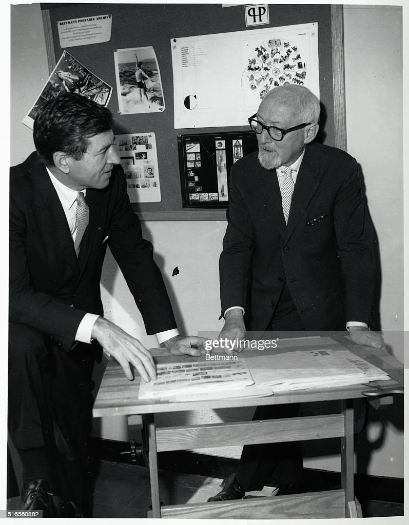 Dr. Otto Bettmann (L) looks over images with an unidentified man for the Bettmann Portable Archive. Undated photograph, circa 1960.