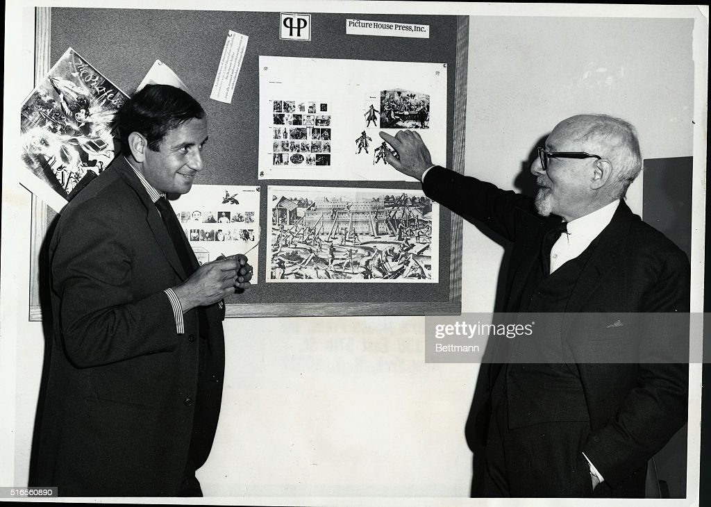 Dr. Otto Bettmann shows pictures from the Bettmann Portable Archive to Mr. Henry Woolf, a graphic designer. Undated photograph circa 1960.