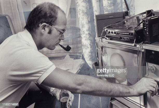 Hunter S Thompson adjust the controls of a television set tuned in to the Watergate hearings during a stay at the SherryNetherland Hotel in New York...