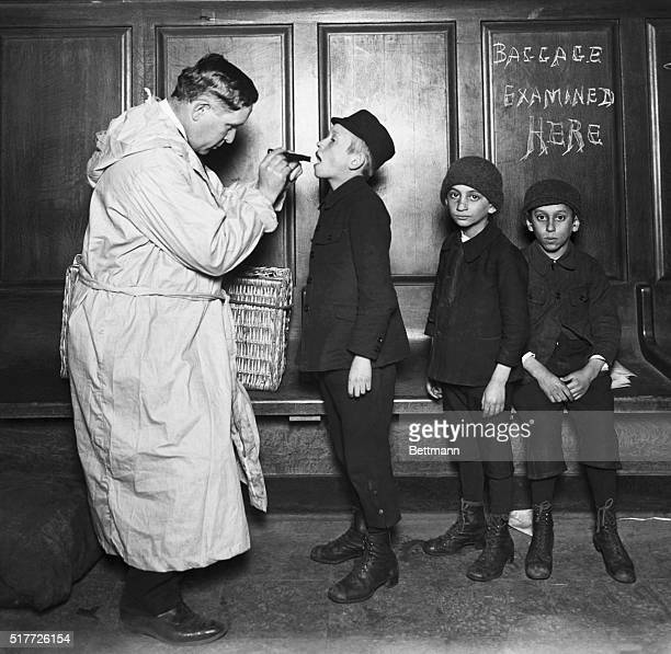 New York, NY: Immigrant children being examined by city health officer upon arrival at the battery from Ellis Island during Typhus Scare. Photograph,...