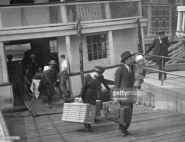 Immigrants leaving a barge at Ellis Island after inspection Photograph