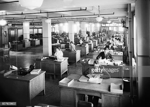 Interior of a large business office in New York City There is a row of a dozen men at their desks next to them are two rows of secretaries Photo ca...