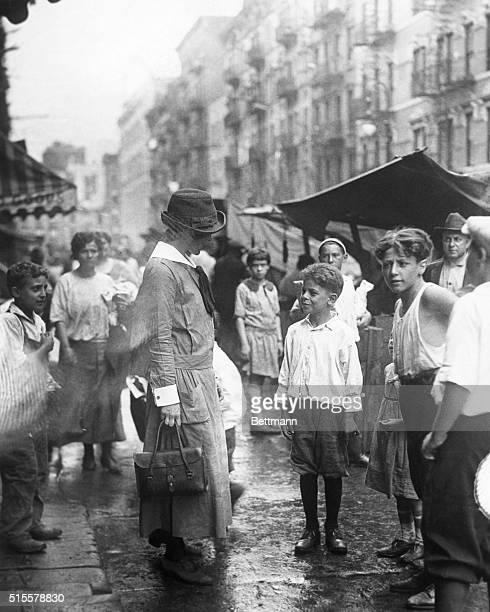 New York, NY: Lower New York street scene showing underprivileged children speaking to visiting nurse from Henry Street settlement house. Photograph,...