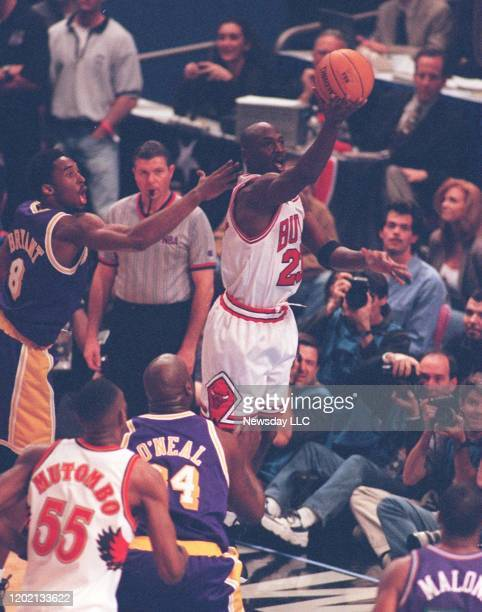 Michael Jordan of the Chicago Bulls on the East team laying the ball up in front of Kobe Bryant of the Los Angeles Lakers on the West team during the...