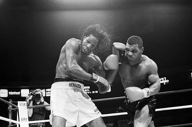 New York, NY- Mitch Green's hair goes flying as undefeated Mike Tyson rocks him with a fistic barage during their 5/20 bout here. Tyson won the fight...