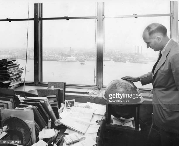 Nathaniel Abelson, chief of the United Nations map department, checks over a globe at his desk overlooking the East River in Manhattan on September...
