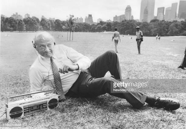 New York City Mayor Ed Koch demonstrates the proper manner in which to listen to a radio or boom box outdoors as he poses with headphones at Sheep...