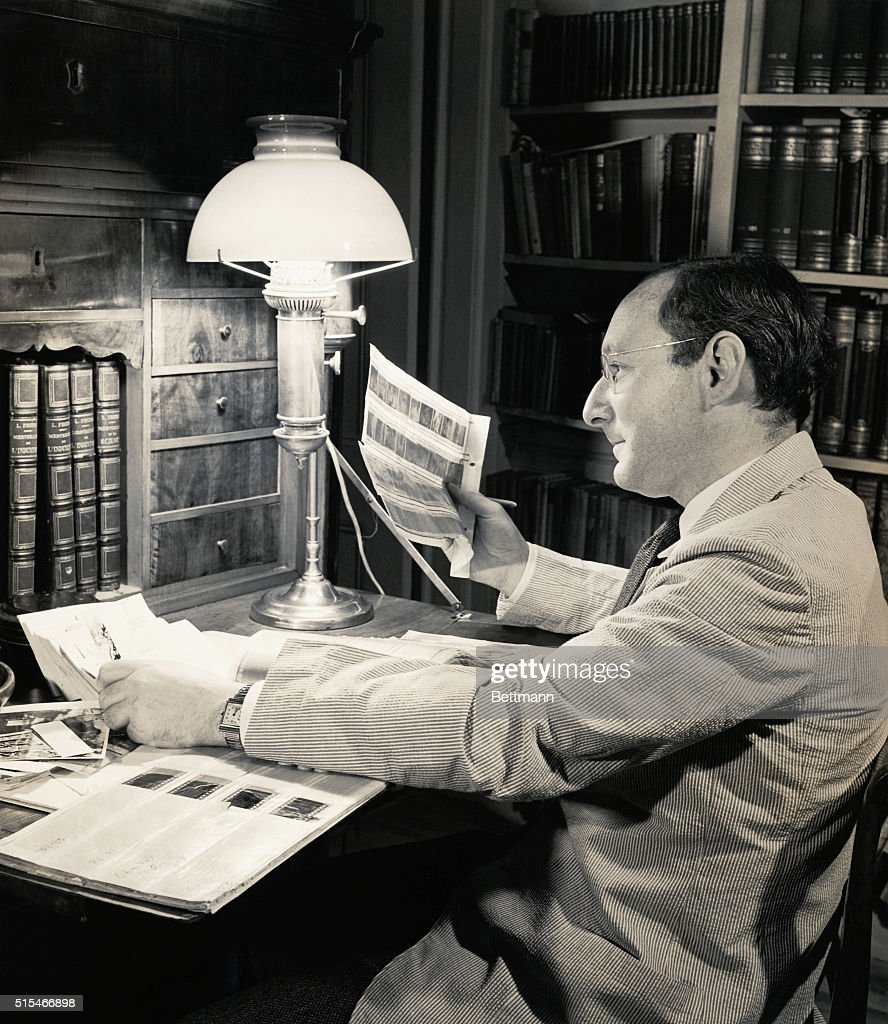 Otto Bettmann examines a sheet of negatives in his study. Undated photograph circa 1930s.