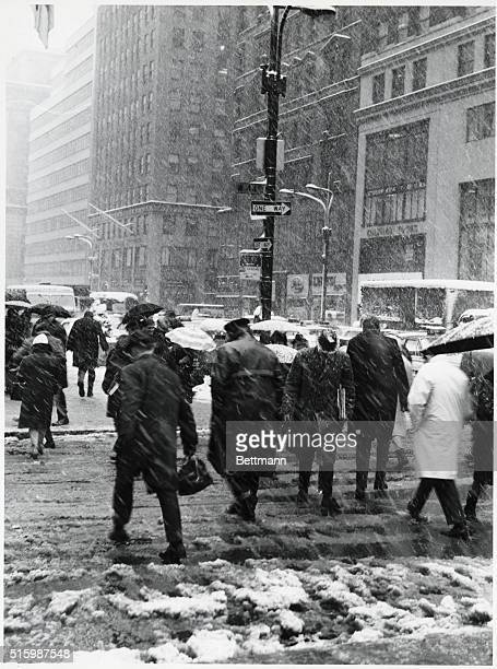 Photo shows pedestrians walking in a snowstorm They are shown on the corner of 44th Street and Fifth Avenue Undated