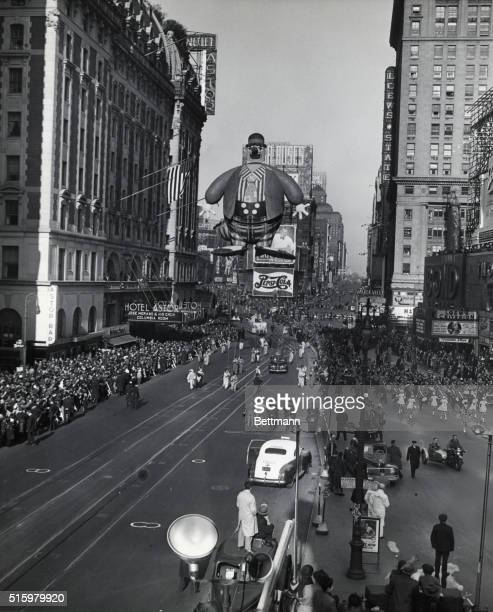 Photo shows the Macy's Thanksgiving Day Parade Attendants drag a huge balloon of a hobo clown down the street as spectators enjoy the sights In the...