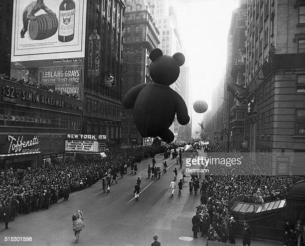 Photo shows the Macy's Thanksgiving Day Parade Giant balloons are led down the street by attendants past sidewalks crowded with spectators Ca 1930