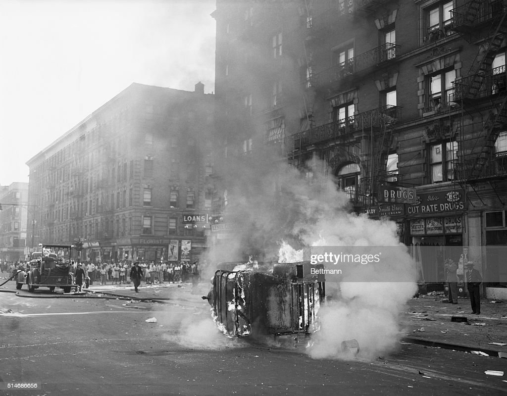 Riot damage. Overturned and blazing, this car is one of many that were wrecked during the riot that swept Harlem, New York's negro section, last night and continued through this morning. Although damage cannot yet be estimated, over 30 shops have been looted, three are dead, and 19 have been injured thus far.
