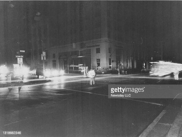 Scene at the corner of 34th Street near the Empire State Building in Manhattan as people use flashlights in circular motion to direct traffic due to...