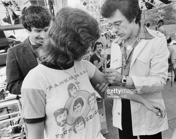 Sharon Ruta of Brooklyn gets her Four Seasons tee shirt signed by musician Frankie Valli before Valli's rehearsal for his concert at Wollman Rink in...