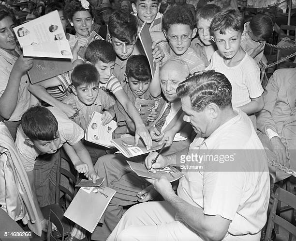 """New York, NY: Small fry mob """"the Babe."""" The mighty Babe Ruth autographs score cards for youngsters who mobbed him as he entered the stands for the..."""