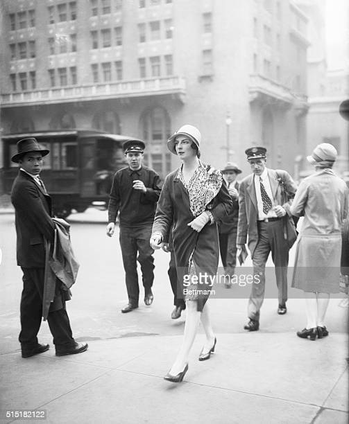 New York, NY- Society Matron Mrs. Robert McAdoo walks down Park Ave. Photograph shows her crossing the street with onlookers.