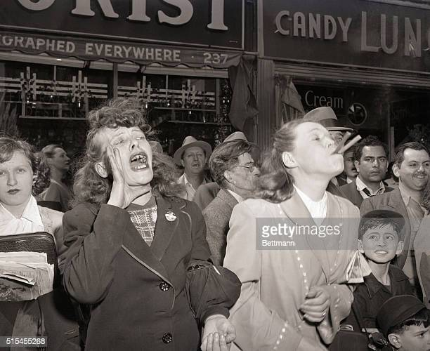 5/1/1951 New York NY The crowd along 8th Avenue heckles the Communist May Day parade in New York City Photo shows one woman blowing a noise maker...