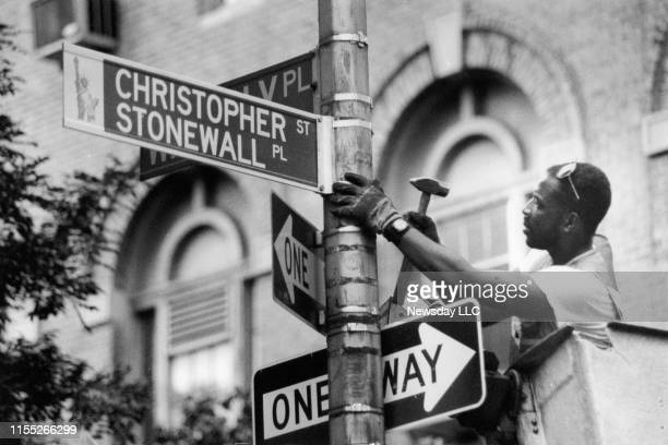 Traffic device worker Darryl Beckles changes the street sign on Christopher Street in Greenwich Village in Manhattan to Christopher Street/Stonewall...