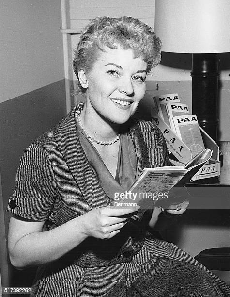 New York NY TV star Patti Page checks her timetable at NY international airport before boarding a Pan American World Airways Clipper for Montego Bay...