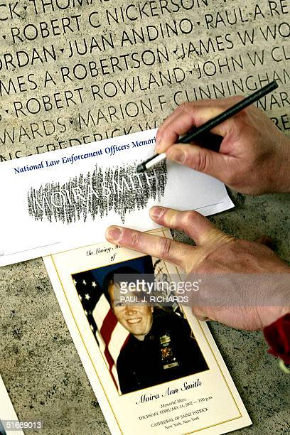 New York Patrolman's Benevolent Association representative Daniel Gravius from the Bronx, NY, stencils the name of NYPD police officer Moira Smith...